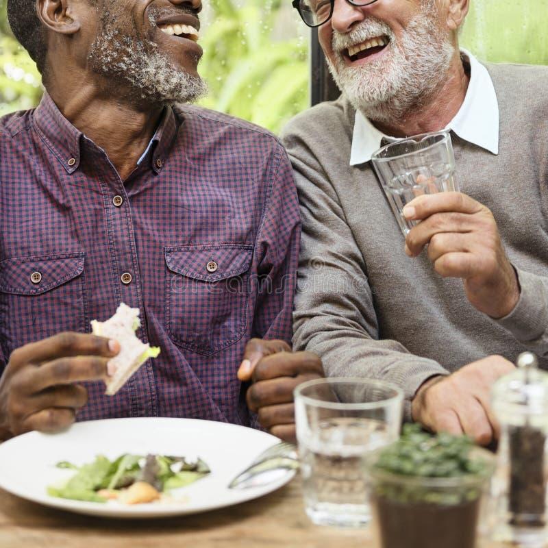 Gli uomini senior si rilassano lo stile di vita che pranzano il concetto immagini stock
