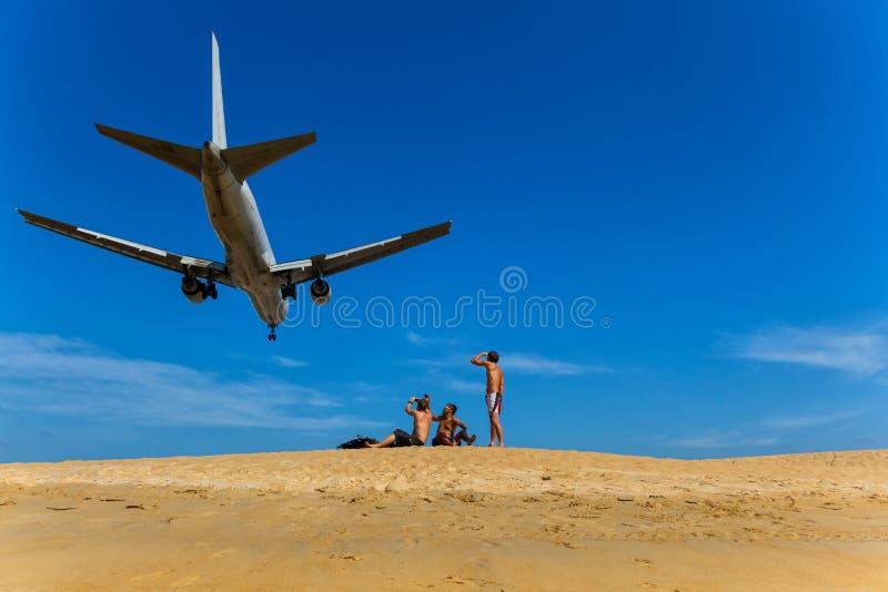 Gli uomini si siedono sulla spiaggia e li esaminano su un aereo che sorvolano sopra fotografia stock libera da diritti