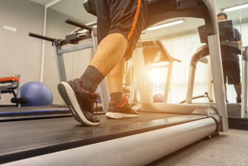 Gli uomini stanno esercitando correndo su una pedana mobile dopo il lavoro in un centro di forma fisica dell'interno di attività  immagine stock