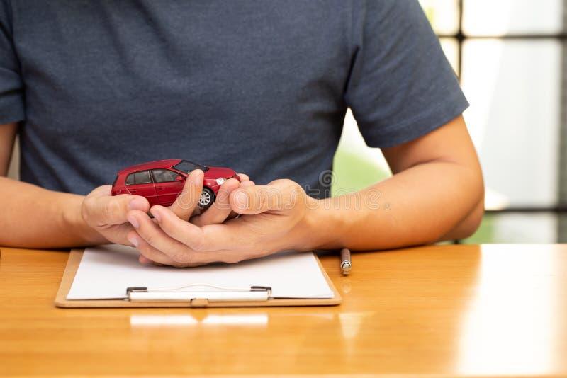 Gli uomini stanno scegliendo di comprare e firmare la polizza dei contratti con il veicolo e l'assicurazione auto, fotografie stock libere da diritti