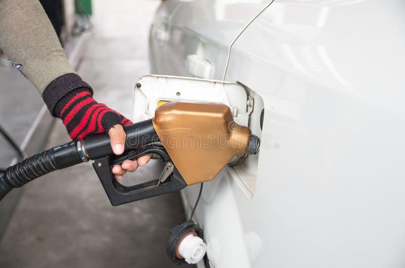 Gli uomini tengono l'iniettore per aggiungere il combustibile in automobile alla stazione di servizio fotografia stock
