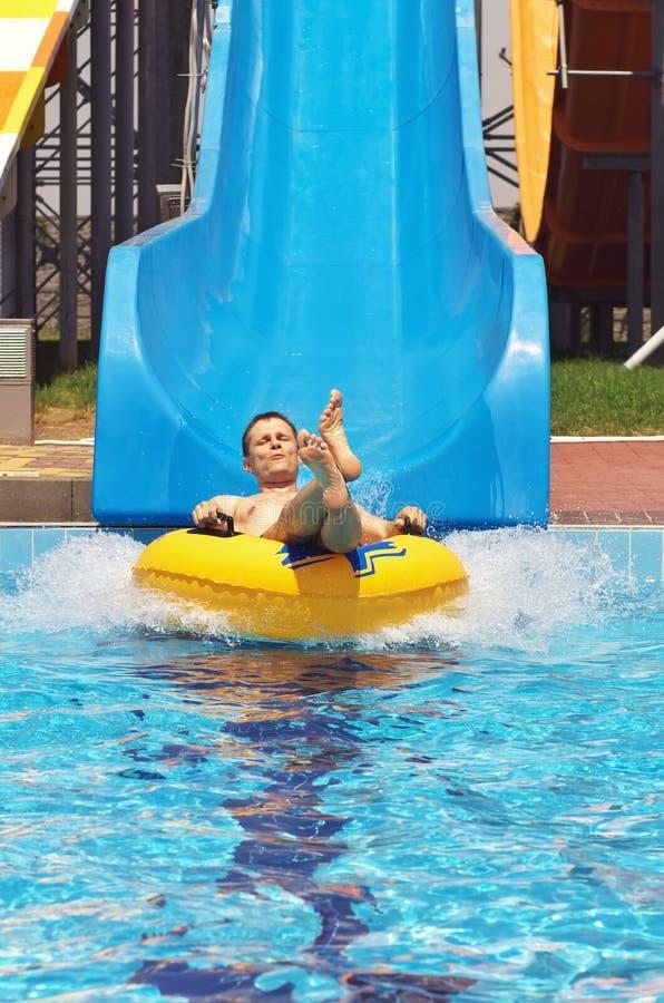 Gli uomini vanno giù dall'acquascivolo alla piscina nel parco dell'acqua Happ immagine stock
