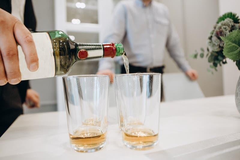 Gli uomini versano insieme la stanza dell'interno del whiskey della bevanda fotografie stock libere da diritti