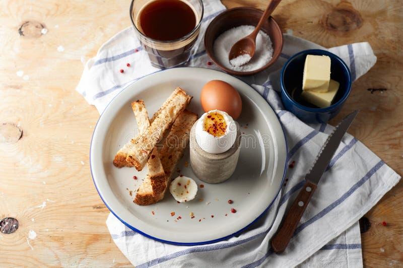 Gli uova sode molli con i soldati imburrati del pane tostato sono una prima colazione inglese classica servita con burro e tazza  immagini stock
