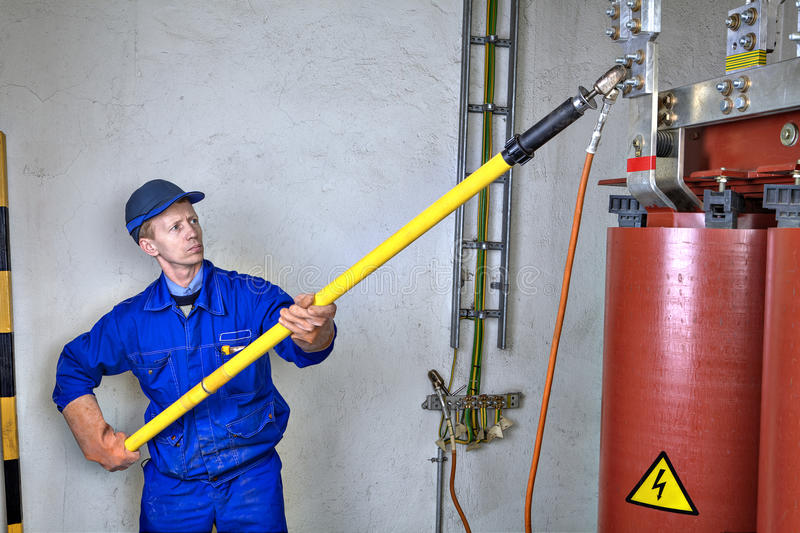 Gli usi dell'ingegnere dell'elettricista scaricano il bastone a terra che collega il tra a massa immagini stock libere da diritti
