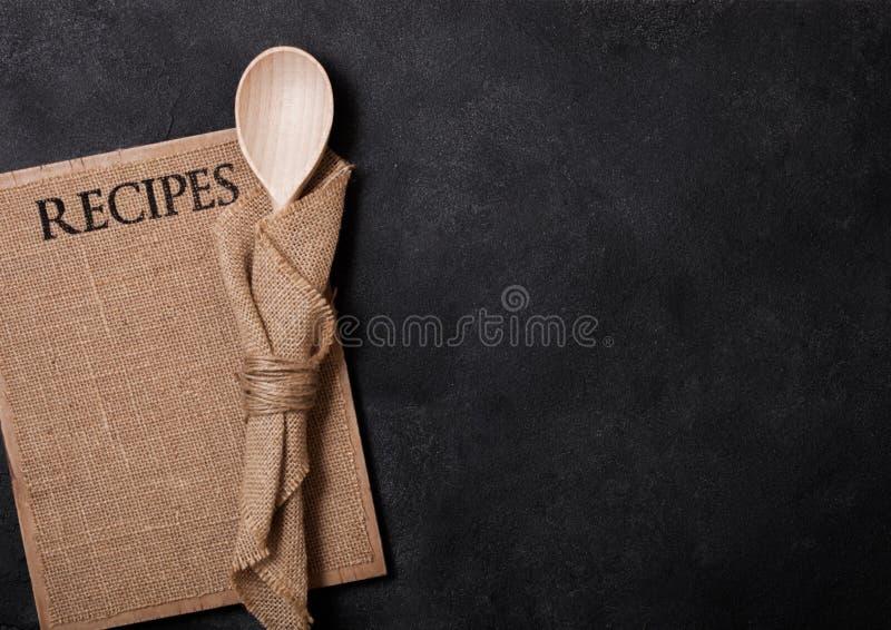Gli utensili di legno della cucina d'annata con le ricette di tela imbarcano sul fondo di pietra nero della tavola Vista superior fotografie stock libere da diritti