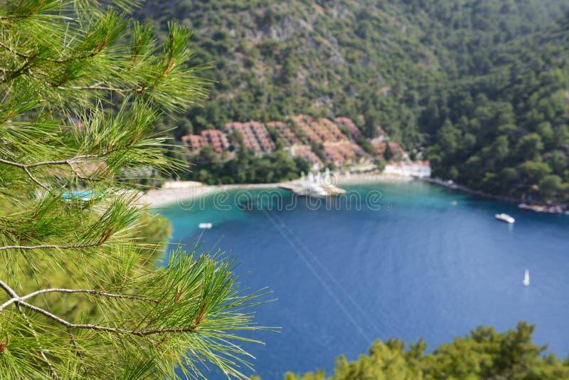 Gli yacht al pilastro ed alla spiaggia sulla località di soggiorno turca Mediterranea, Fethiye, fuoco della Turchia è sul pino immagini stock libere da diritti