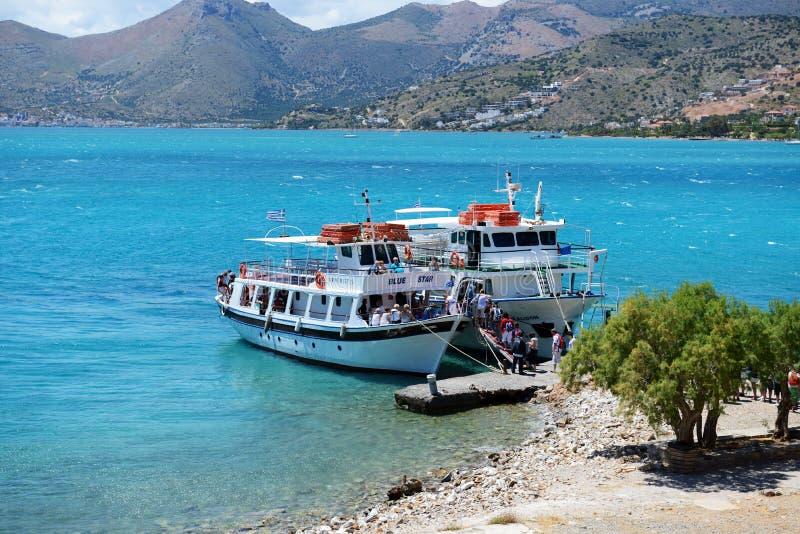 Gli yacht del motore con i turisti sono vicino all'isola di Spinalonga fotografie stock