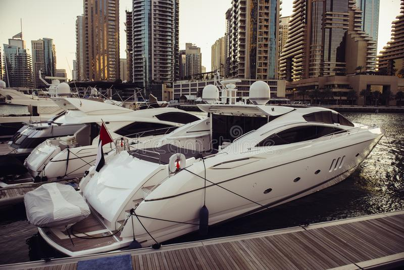 Gli yacht di lusso hanno parcheggiato sul pilastro nella baia del porticciolo del Dubai con la vista della città immagini stock