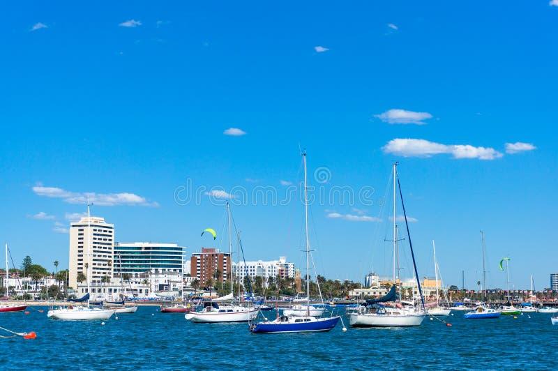 Gli yacht e le barche con la spiaggia della città abbelliscono sui precedenti fotografia stock libera da diritti