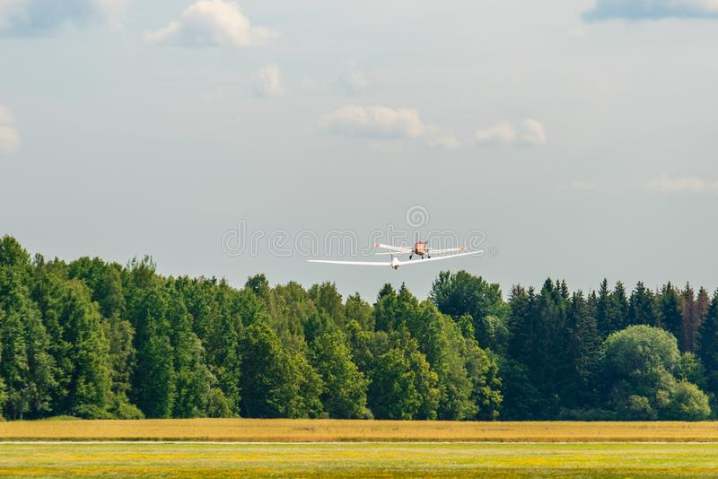 Glider being pulled up in the air by a small aircraft. Wide winged sailplane or glider being pulled up in the air by a small aircraft on a small airfield in stock image