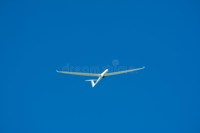 Glider in flight. A glider (sailplane) aloft, set against an azure blue sky royalty free stock image