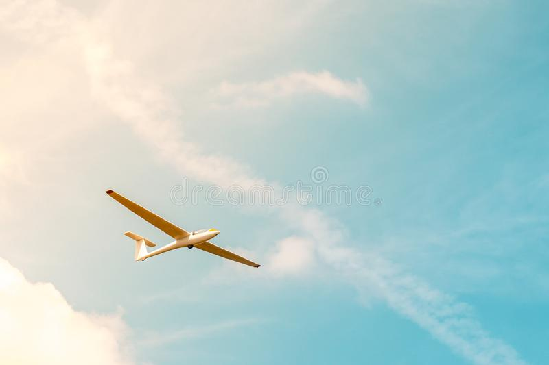 Glider flying against the blue sky with clouds and sunlight.  stock image