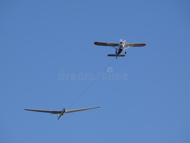 Glider pulled by a motorized plane. Glider airplane stands out f stock image