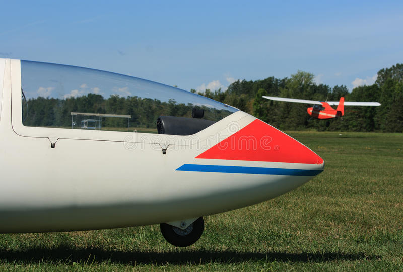 Glider and Tow Plane. A glider on the ground with a tow plane landing in the background in Manotick, Ontario, Canada stock photos