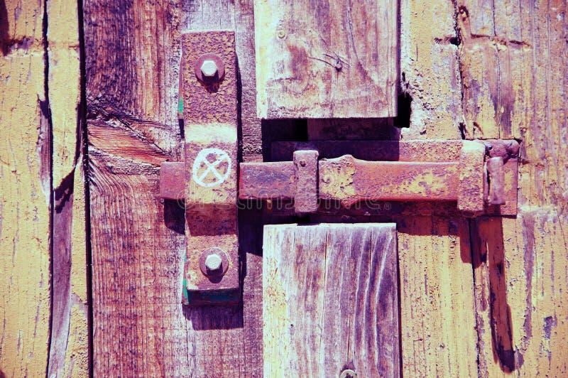 Glidningsbult med motstycken på den gamla träporten royaltyfria bilder