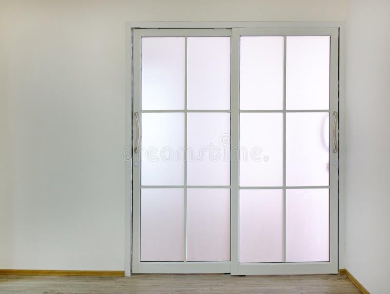 Glidningsdörr med genomskinligt exponeringsglas i tomt rum fotografering för bildbyråer