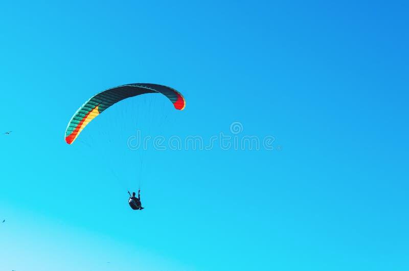 Glijscherm die op kleurrijk valscherm in blauwe duidelijke hemel bij een heldere zonnige de zomerdag vliegen Actieve levensstijl, royalty-vrije stock foto's