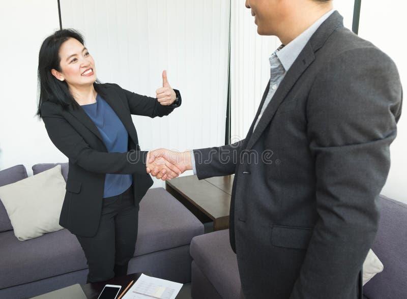 Glimlach het Bedrijfsvrouw en bedrijfsman schudden hand en duim omhoog stock foto's