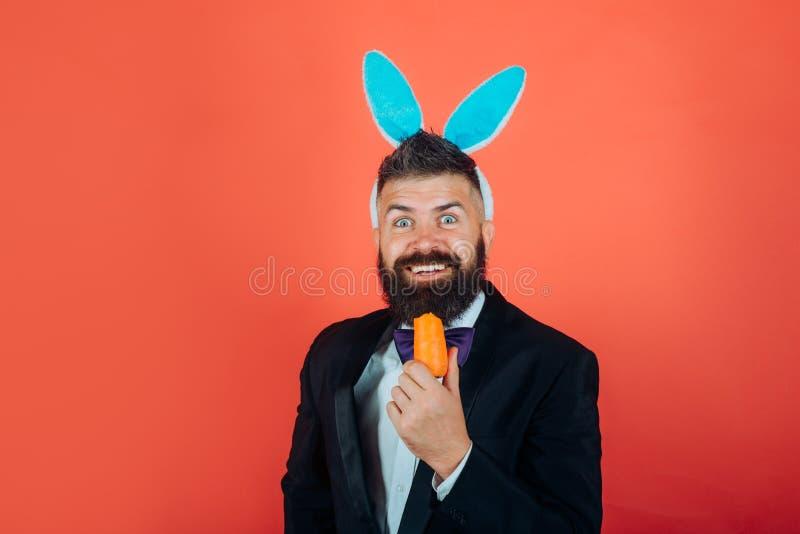 Glimlach Pasen Gelukkige Pasen en grappige Pasen-dag De mens die van het konijntjeskonijn met konijntjesoren Pasen vieren stock foto