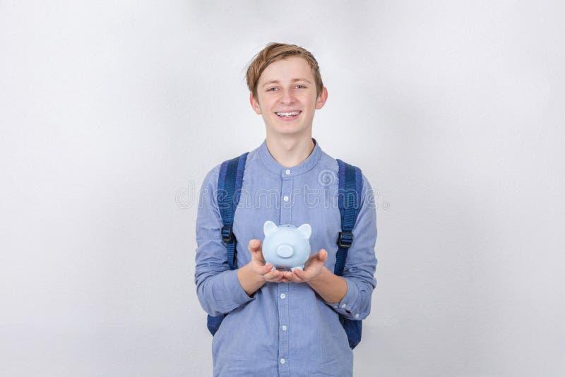 Glimlach Teenager houdt spaarpot boven witte achtergrond Geconcept voor besparingen op financieel onderwijs stock afbeelding
