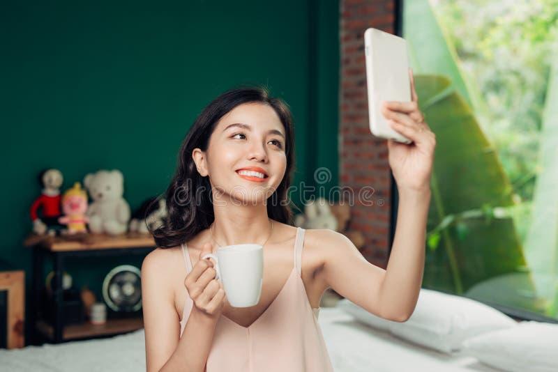Glimlach van de gezondheids neemt de Aziatische vrouw een selfie en zij zitting op is stock afbeeldingen
