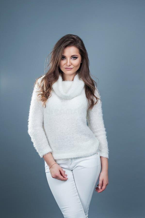 Glimlach van het portret de jonge mooie meisje en het dragen van gebreide witte sweater, op grijze achtergrond royalty-vrije stock foto