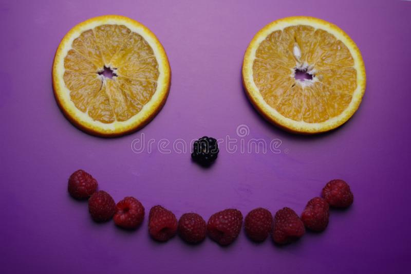 Glimlach van vers bessen en fruit op de purpere achtergrond stock afbeelding