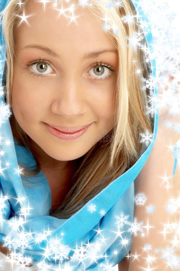 Glimlachen blond in blauwe sjaal met sneeuwvlokken royalty-vrije stock afbeelding