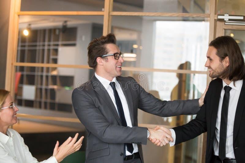 Glimlachen CEO die mannelijke manager met baanbevordering gelukwensen stock foto