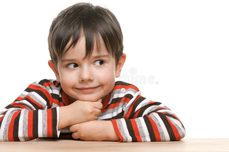Glimlachen slim weinig jongen bij het bureau stock foto's