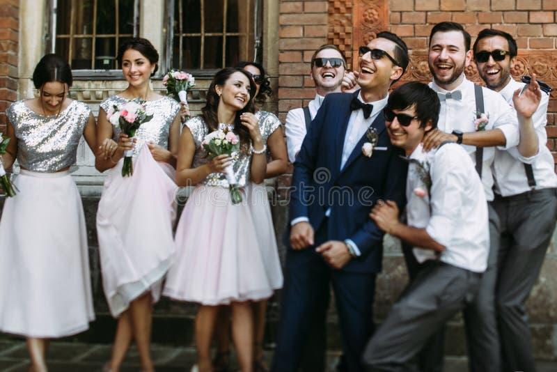 Glimlachen van de bruidegom met bruidsmeisjes en groomsmen stock fotografie