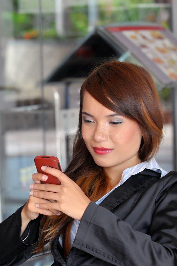 Glimlachen van jonge Aziatische onderneemster die handph texting stock foto