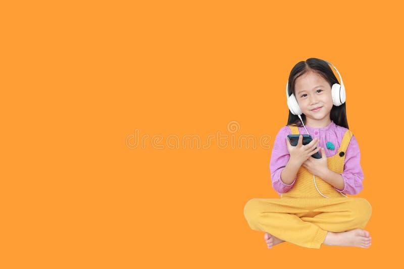 Glimlachen van weinig Aziatisch meisje geniet van luister aan muziek door hoofdtelefoons en kijkend recht geïsoleerd over oranje  royalty-vrije stock foto