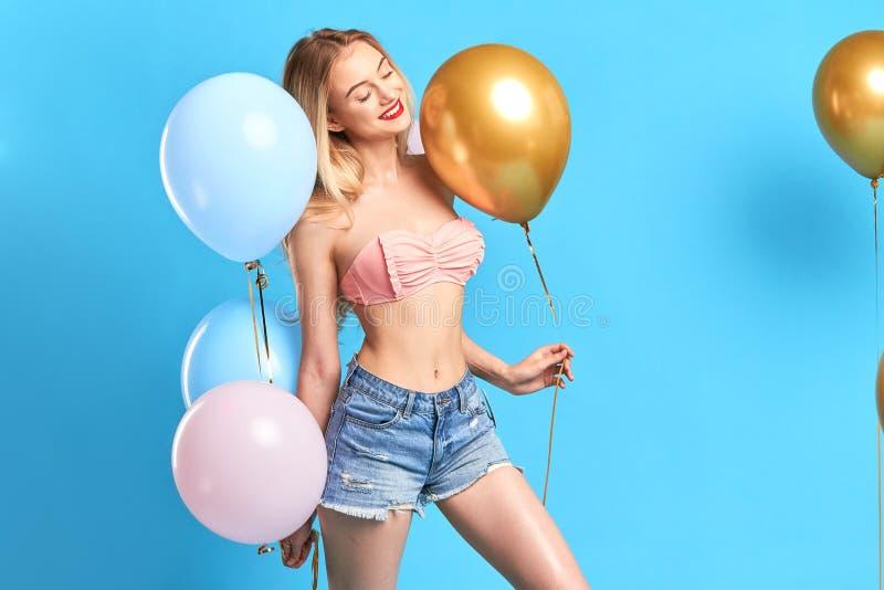 Glimlachend aantrekkelijk elegant meisje dat met gesloten ogen ballons houdt stock afbeelding