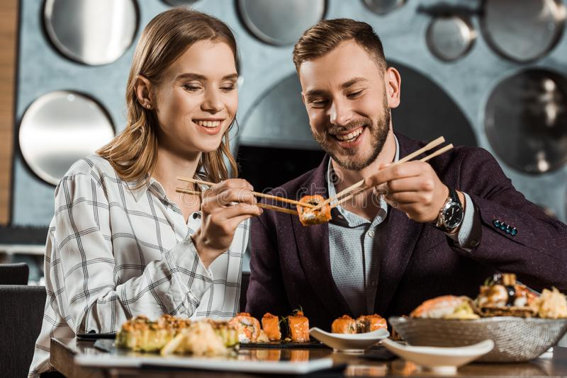 Glimlachend aantrekkelijk jong volwassen paar die sushi samen eten stock fotografie