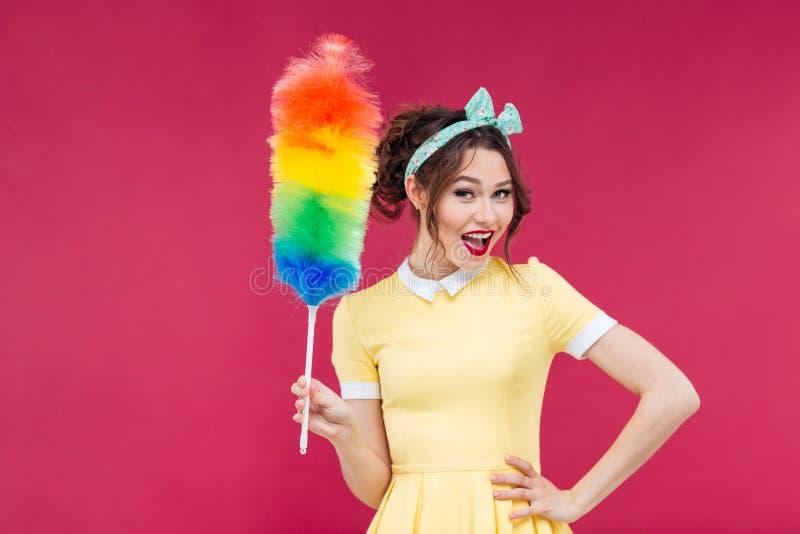 Glimlachend aantrekkelijk pinupmeisje die kleurrijke stofdoekborstel houden royalty-vrije stock foto's