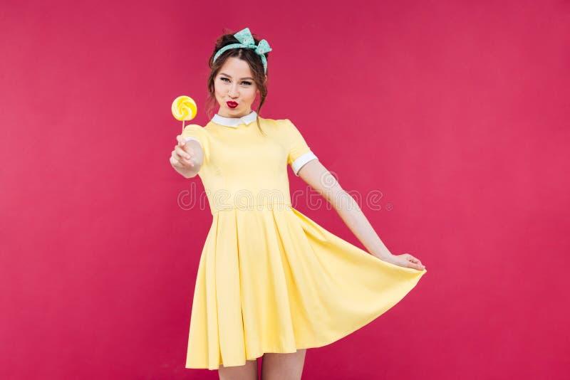 Glimlachend aantrekkelijk pinupmeisje in gele kleding die zoete lolly tonen stock foto's