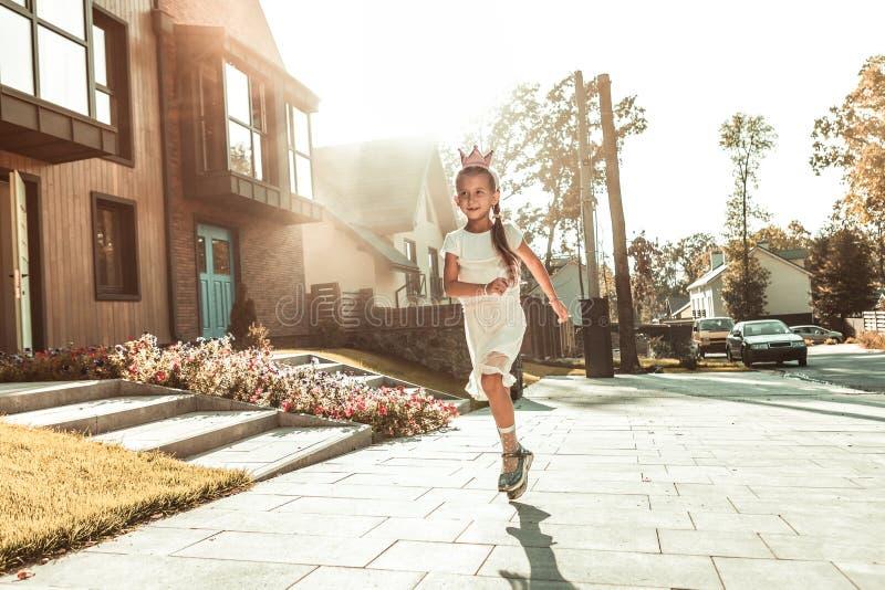 Glimlachend actief meisje in witte mooie kleding en leuke kroon royalty-vrije stock foto