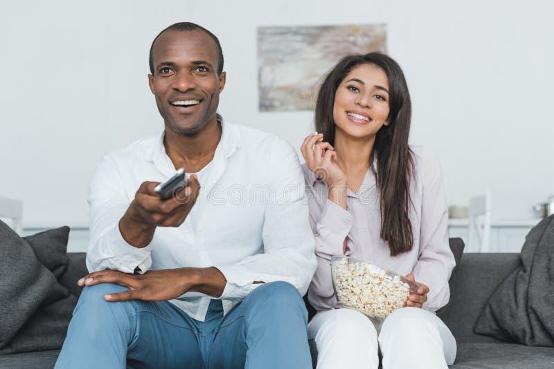 glimlachend Afrikaans Amerikaans paar die op TV met popcorn letten stock foto's