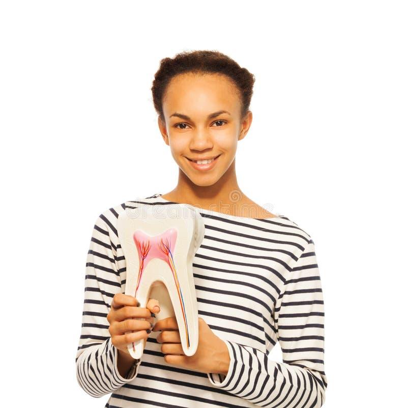 Glimlachend Afrikaans meisje die tandstructuur bestuderen stock afbeeldingen