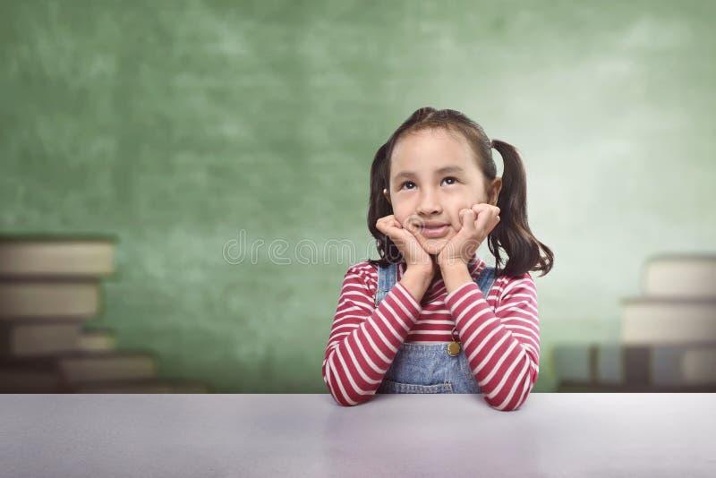 Glimlachend Aziatisch kind die met grappige uitdrukking denken stock afbeeldingen