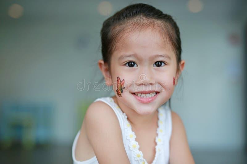 Glimlachend Aziatisch kindmeisje met de sticker van de vlindertatoegering op wang, kleed omhoog tatoegeringenconcept stock fotografie