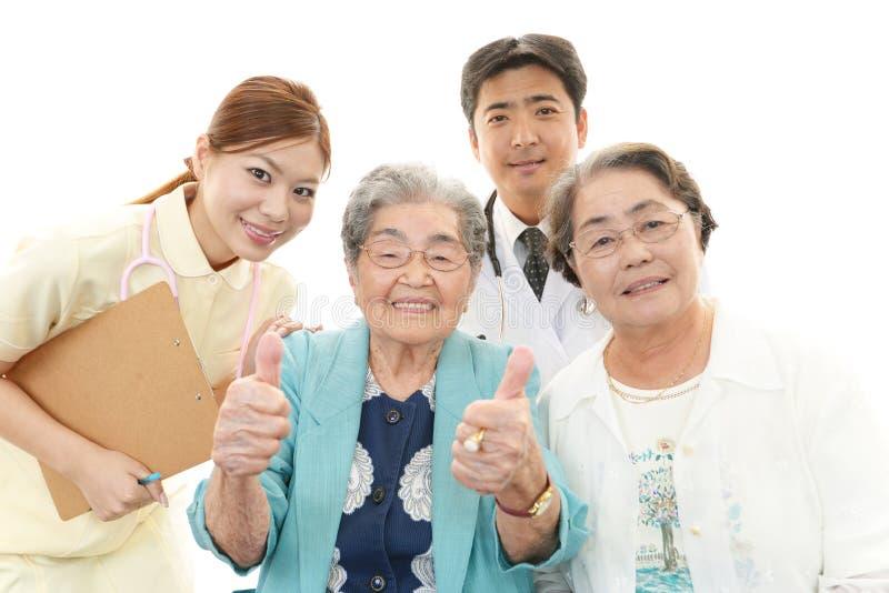 Glimlachend Aziatisch medisch personeel met oude vrouwen royalty-vrije stock foto's