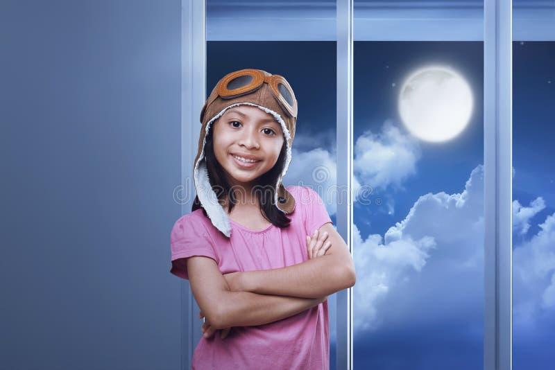 Glimlachend Aziatisch meisje beschermende brillen dragen en vliegenier GLB die zich in h bevinden royalty-vrije stock fotografie