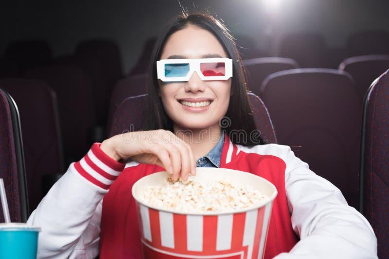 glimlachend Aziatisch meisje in 3d glazen met grote mand van popcorn het letten op film royalty-vrije stock foto