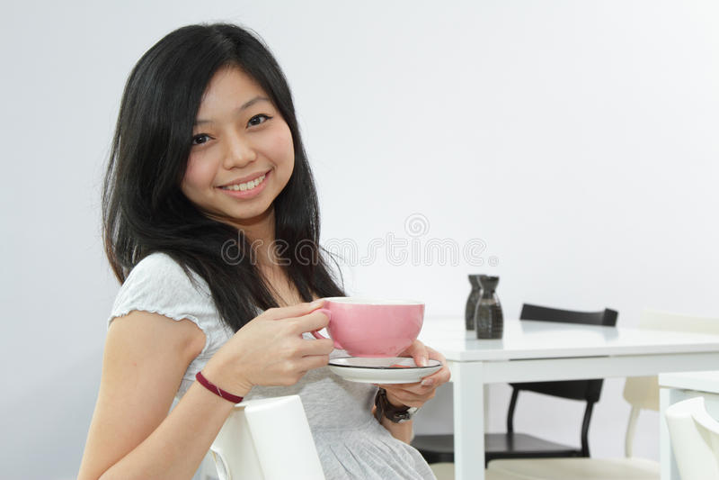 Glimlachend Aziatisch meisje met koffie royalty-vrije stock foto's