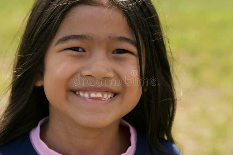 Glimlachend Aziatisch meisje met toothy glimlach