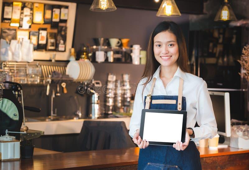 Glimlachend Aziatische de holdings lege tablet van vrouwenbarista verwerk in fron gegevens stock afbeelding