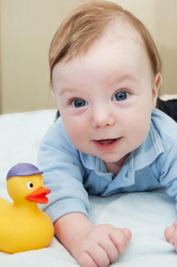 Glimlachend babyjongen en stuk speelgoed stock afbeeldingen